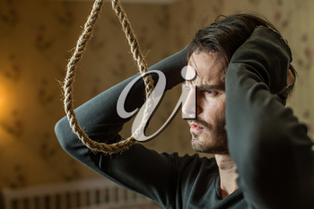 Desperate man preparing to commit suicide. Depressed man with a rope noose.