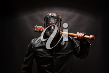 Psycho killer in hockey mask with bloody bat on black background.