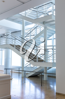 Marble floor and metal staircase in modern building with white interior.