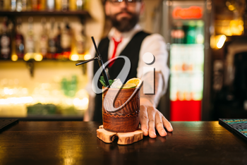 Barkeeper shows attractive alcoholic cocktail. Handsome alcohol beverage preparation