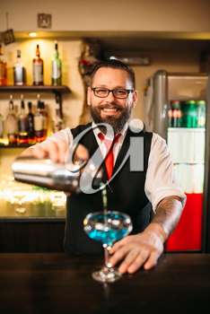 Bartender with shaker making alcohol cocktail behind a bar counter