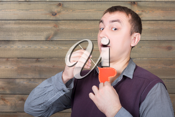 Young playful man with funny red heart on a stick, wooden background. Fun photo props and accessories for shoots