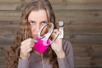Young female with funny pink heart on a stick, wooden background. Fun photo props and accessories for shoots