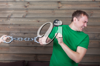 Young man handcuffed to marriage shows funny icon on a stick with  just married inscription, wooden background. Fun photo props and accessories for shoots
