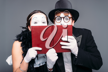 Two comedy performers posing with book. Pantomime theater actor and actress performing