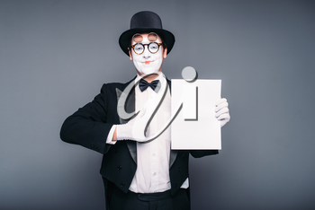 Pantomime actor performing with empty paper sheet. Comedy mime artist in suit, gloves, glasses, make-up mask and hat