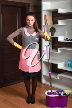 Young housemaid woman in cleaning servisce uniform and rubber gloves holds mop in hands. Housekeeping concept