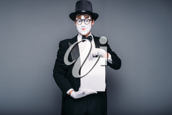 Male mime actor with empty paper sheet. Pantomime in suit, gloves, glasses, make-up mask and hat. April fools day concept