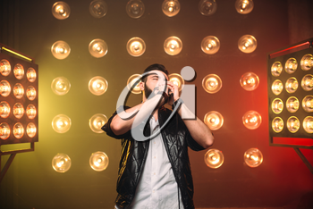 Brutal bearded singer with microphone on the stage with the decorations of lights
