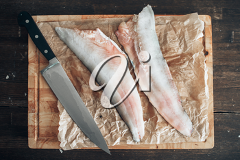 Raw fish slices and knife on cutting board covered with parchment paper, top view