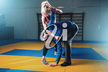 Male and female fighters, self defense technique, self-defense workout with personal trainer in gym, martial art