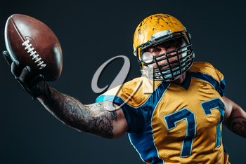 American football offensive player with ball in hand, national league, black background. Contact sport
