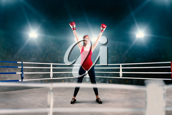Female boxer in red bandages and sportswear hands up on the ring, side view. Winner woman on boxing ring