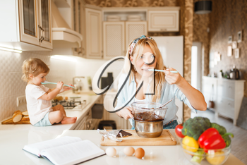Young mother and her daughter tastes melted chocolate. Cute woman and little girl cooking on the kitchen, pastry preparation. Happy family prepares sweet dessert at the counter