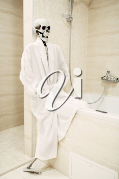 Human skeleton in white bathrobe sitting on the edge of the bath in bathroom, black humor