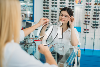 Female optician and consumer chooses glasses frame in optics store. Selection of spectacles with professional optometrist