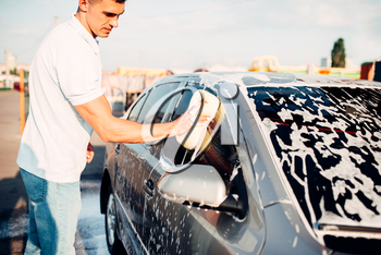 Washer rubbing vehicle with foam, automobile in suds, car wash. Carwashing station