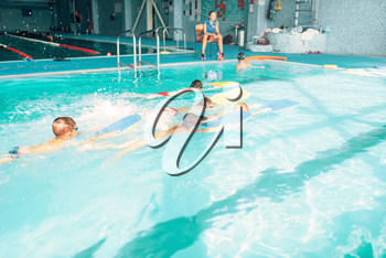 Boys swimming with plank in a pool race. Children in water with plank are doing swim exercise. Healthy sport activity in pool. Sportive kids activity in modern sport center with pool.