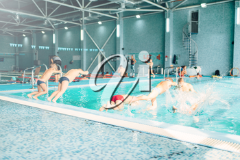 Kids jumping into pool with clean blue water. View from back. Children learn to swim and dive. Modern sports center on background. Sportive kids activity.