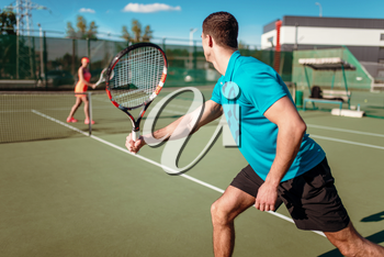 Athletic man and slim woman on tennis training on outdoor court, players with rackets. Summer season active sport game