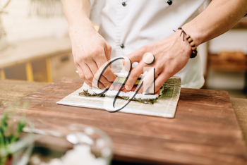 Male cook making seafood on wooden table, asian kitchen preparation process. Traditional japanese cuisine, sushi ingredients