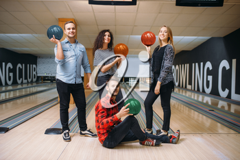 Bowling team poses on lane with balls on hands. Players before competition. Friends playing classical tenpin game in club, active leisure