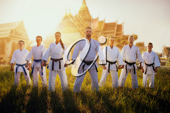 Male and female karate group in kimono against ancient temple on sunset. Martial art training outdoor. Photo manipulation with background