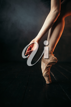 Ballerina hand and legs in pointes, black wooden floor. Ballerina in red dress and black practice dancing on the stage in theatre