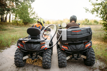 Two atv riders in helmets, back view. Freeriding on quad bike, extreme sport and travelling, quadbike summer adventure
