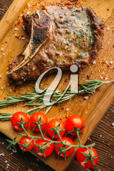 Juicy grilled steak on the bone and tomatoes on a branch closeup, nobody. Meat dish on wooden table