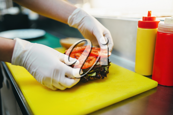 Male cook puts tomatoes in to the burger, fast food cooking. Hamburger preparation process, fastfood