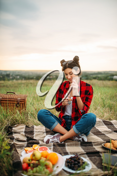 Cute woman with glass of wine reads book, picnic on meadow. Romantic junket, happy holiday