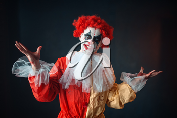 Portrait of scary bloody clown with crazy eyes. Man with makeup in carnival costume, mad maniac