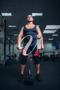 Strong male athlete prepares for exercise with kettlebell lifting. Weightlifting workout in sport or fitness club, weight lifter on training in gym