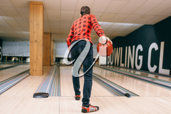 Male bowler throws ball on lane, back view. Bowling alley player playing tenpin game in club, active leisure