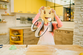 Little girl chef made a funny face out of dough, cookies preparation on the kitchen, funny baker. Kids cooking pastry, child cook, children preparing cake