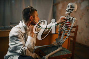 Male psychiatrist with stethoscope listening the skeleton, mental hospital. Doctor in clinic for the mentally ill