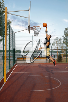 Basketball player makes shoot in jump. Male athlete in sportswear scores on streetball training