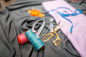 Fabric, thread, and scissors in textile store, nobody. Showcase with acessories for sewing, clothing choice in shop