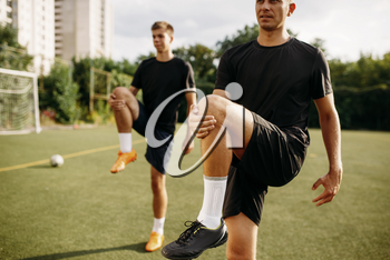 Two male soccer players doing stretching exercise on the field. Football training on outdoor stadium, workout before game