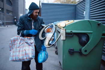 Male bearded beggar searching food in trashcan on city street. Poverty is a social problem, homelessness and loneliness, alcoholism and drunk addiction, urban lonely