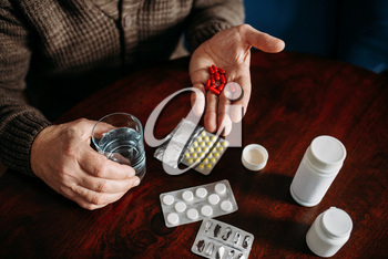 Elderly man hand with pills, home office on background, age-related diseases. Mature senior is ill and being treated in his house