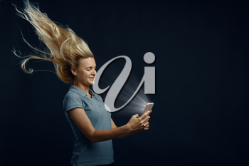 Woman looking on phone against powerful airflow in studio, back view, developing hairstyle effect. Female person and wind, lady isolated on dark background