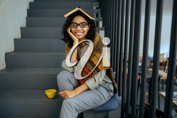 Pretty female student with book sitting on the steps in library cafe. Woman learning a subject, education and knowledge. Girl studying in campus