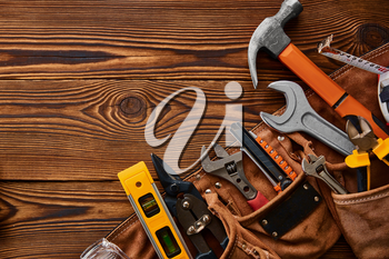 Professional workshop instrument, macro view, wooden background, nobody. Carpenter tools, builder equipment, screwdriver and wrench, piles and metal scissors, hammer and level