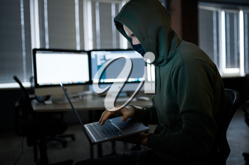 Male internet hacker in hood holds laptop, front view. Illegal web programmer at workplace, criminal occupation. Data hacking, cyber safety