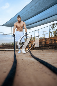 Muscular man doing exercise with ropes, street workout, crossfit. Fitness training on sports ground outdoor, male person pumps muscles, active urban lifestyle