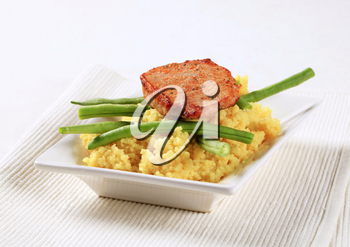 Dish of marinated pork with couscous and green beans
