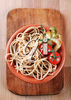 Cooked whole wheat spaghetti in a terracotta bowl