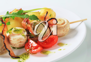Skewer of button mushrooms with crispy bacon and potatoes